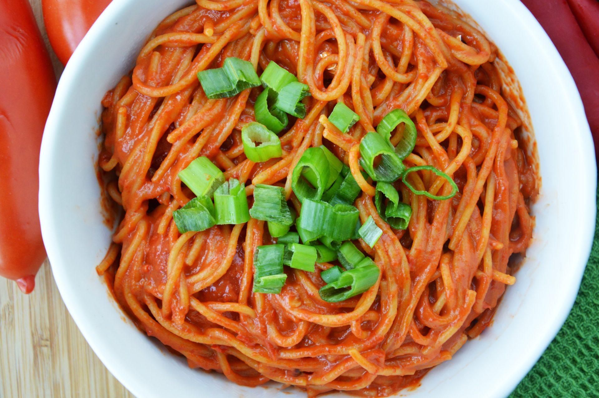 Spaghetti z sosem z pieczonej papryki i masła orzechowego posypane szczypiorkiem